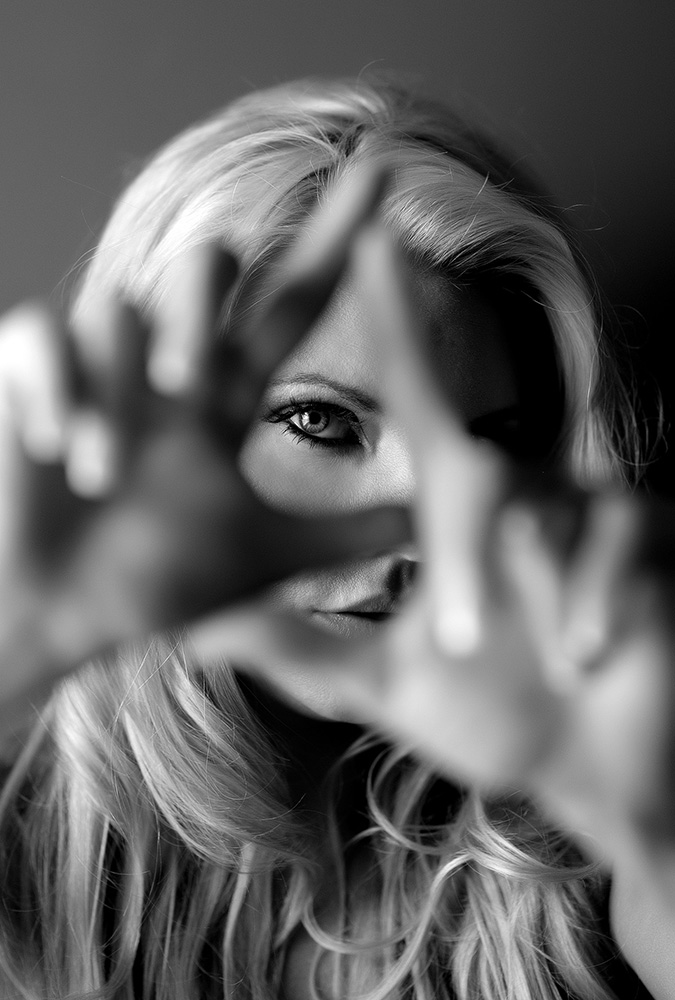 Beautiful blonde woman holding her hands up