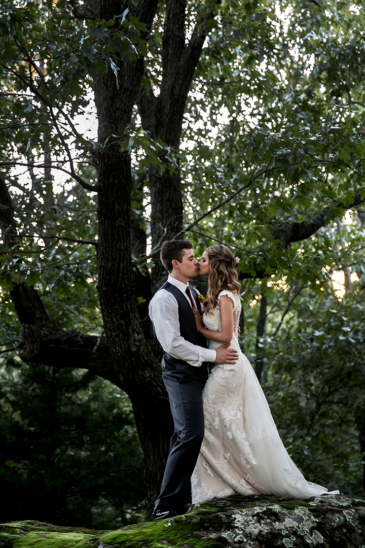 Bride and groom kissing in the woods at Skelly Lodge